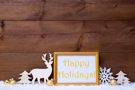 like english: Christmas Card With Picture Frame On White Snow. English Text Happy Holidays. White Decoration Like Snowflake, Tree, Golden Balls And Reindeer. Vintage, Wooden Background