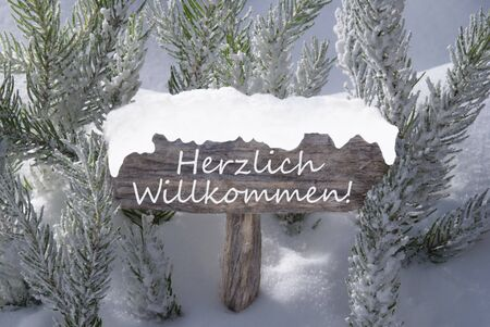 willkommen: Wooden Christmas Sign With Snow And Fir Tree Branch In The Snowy Forest. German Text Herzlich Willkommen Means Welcome For Seasons Greetings Or Christmas Greetings. Christmas Atmosphere.