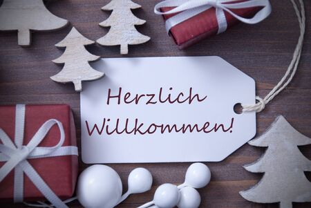 willkommen: Black and White Close Up Of Label With Ribbon,Red Gift,Present, Ribbon And Tree. Christmas Decoration Or Card On Wooden Background. German Text Herzlich Willkommen Means Welcome