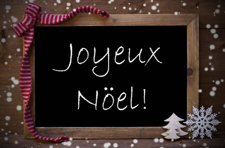 Brown Christmas Blackboard With French Text Joyeux Noel Means Merry Christmas As Greeting Card. Christmas Decoration, Christmas Tree, Snowflakes, Red Loop. Wooden Background. Vintage Rustic Style. Stock Photo