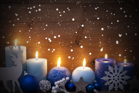 Christmas Decoration With Purple And Blue Candles,Reindeer, Christmas Ball, Snowflakes, Fir Cone,Star. Peaceful Atmosphere With Candlelight. Wooden Background For Copy Space. Vintage Style