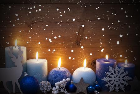 Weihnachtsdekoration mit purpurroten und blauen Kerzen, Rentier, Weihnachtsball, Schneeflocken, Tannenzapfen, Stern. Ruhige Atmosphäre mit Kerzenlicht. Hölzerner Hintergrund für Kopie Raum. Vintage-Stil Standard-Bild