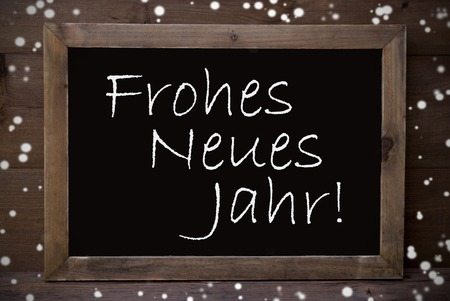 jahr: Brown Blackboard With German Text Frohes Neues Jahr Means Happy New Year As Christmas Greeting Card. Wooden Background. Vintage Rustic Style. Snowflakes Symbolizing Christmas Or Winter Season.