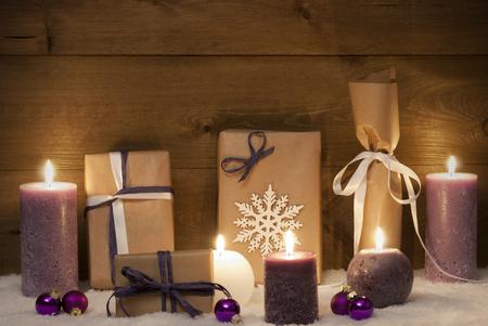 morado: Tarjeta de la decoraci�n o Navidad Con Velas p�rpuras, regalos de Navidad, regalos, bolas de navidad, SnowflakeAnd nieve. Ambiente Tranquilo Con luz de las velas. Fondo r�stico de madera de la vendimia