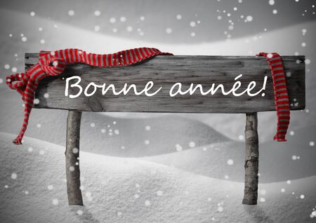 bonne: Gray Wooden Christmas Sign On White Snow. Snowy Scenery, Snowflakes. Red Ribbon, FrenchText Bonne Annee Means Happy New Year. Christmas Decoration Or Card. Rustic Or Vintage Syle.Black And White Image