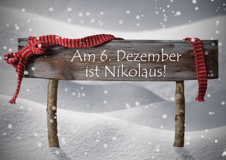 st german: Brown Wooden Christmas Sign On White Snow. Snowy Scenery, Snowflakes. Red Ribbon, German Text Am 6. Dezember Ist Nikolaus Means St. Nicholas Day. Christmas Decoration, Card. Rustic Or Vintage Syle Stock Photo