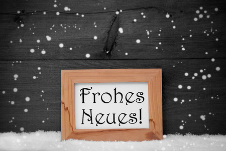 neues: Gray Christmas Card With Brown Picture Frame On White Snow With Snowflakes. German Text Frohes Neues Means Happy New Year. Rustic Wooden, Vintage Background. Black And White