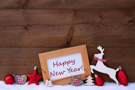 like english: Christmas Card With Picture Frame On White Snow And Sparkling Star. English Text Happy New Year. Red Christmas Decoration Like Christmas Ball, Tree And Reindeer. Wooden, Vintage Background