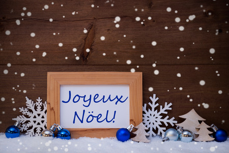 french text: Blue Decoration On Snow. Christmas Tree Balls, Snowflakes And Christmas Tree. Picture Frame. French Text Joyeux Noel Mean Merry Christmas. Rustic, Vintage Brown Wooden Background