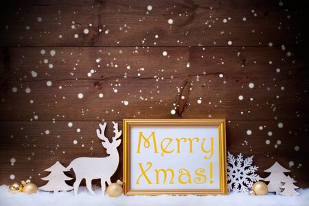 like english: Christmas Card With Picture Frame On White Snow. English Text Merry Xmas. White Decoration Like Snowflakes, Tree, Golden Balls And Reindeer. Vintage, Wooden Background Stock Photo