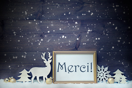 french text: Vintage Christmas Card With Picture Frame On White Snow. French Text Merci Means Thank You. White Decoration Like Snowflakes, Tree, Golden Balls And Reindeer. Shabby Chic, Wooden Background By Night