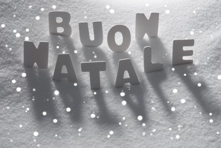 buon: White Letters Building Italian Text Buon Natale Means Merry Christmas On White Snow. Snowy Landscape Or Scenery With Snowflakes. Christmas Card For Seasons Greetings Or Usable As Background. Stock Photo