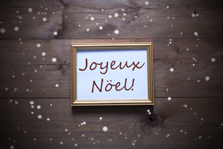 joyeux: One Golden Picture Frame On Wooden Background. French Text Joyeux Noel Means Merry Christmas. Rutic Vintage Or Retro Style. Snowflakes For Christmas Or Winter Atmosphere. Card For Seasons Greetings Stock Photo