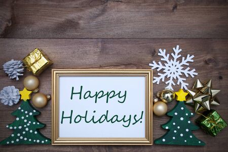 like english: Golden Picture Frame With Green Tree And Christmas Decoration Like Gifts, Balls Snowflake And Fir Cone. English Text Happy Holidays. Brown Wooden And Rustic Retro Background As Christmas Card.