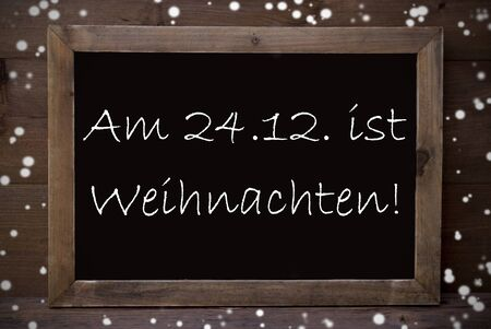 greeting season: Brown Blackboard With German Text Am 24.12 Ist Weihnachten Means Merry Christmas As Greeting Card. Wooden Background. Vintage Rustic Style. Snowflakes Symbolizing Christmas Or Winter Season.