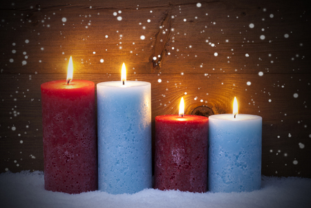 candlelight: Christmas Decoration With Red And Blue Candles. Four Candle For Advent. Peaceful, Romantic Atmosphere With Candlelight And Snowflakes. Wooden, Vintage, Rustic Background By Night