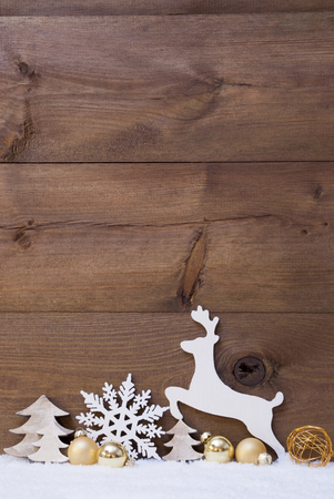 happy holidays card: Vertical Christmas Card With White And Golden Christmas Decoration On Snow. Copy Space For Advertisement. Decoration Like Snowflake, Balls, Tree And Reindeer. Vintage, Rustic Wooden Background.