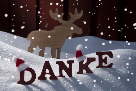 santa moose: Red Letters With Santa Hat On White Snow With Snowflakes As Christmas Card.  German Text Or Word Danke Mean Thank  You. Moose In Snowy Scenery And Atmosphere. Rustic Vintage Wooden Background