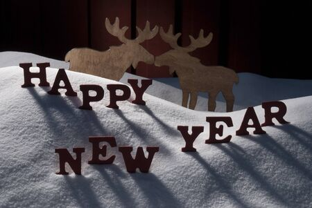 realtionship: Red Letters On White Snow As Christmas Card.  English Text Or Word Happy New Year. Moose Couple In Love In Snowy Scenery And Atmosphere. Rustic Vintage Wooden Background