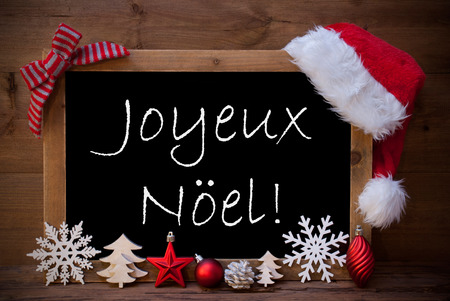 joyeux: Blackboard With Red Santa Hat And Christmas Decoration like Snowflake, Tree, Christmas Ball, Fir Cone, Star. French Text Joyeux Noel Means Merry Christmas. Brown Wooden Background