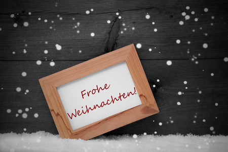 frohe: Gray Christmas Card With Brown Picture Frame On White Snow With Snowflakes. German Text Frohe Weihnachten Means Merry Christmas. Rustic Wooden, Retro Vintage Background. Black And White