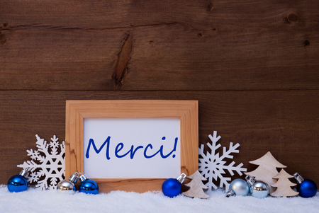 french text: Blue Christmas Decoration On Snow. Christmas Tree Balls, Snowflake And Christmas Tree. Picture Frame With French Text Merci Means Thank You. Rustic, Vintage Brown Wooden Background.