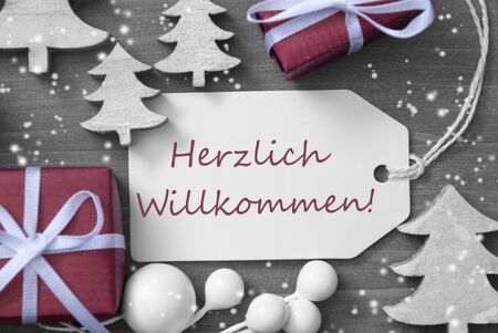 willkommen: Black and White Close Up Of Label With Ribbon,Red Gift,Present, Ribbon And Tree With Snowflakes. Christmas Decoration Or Card On Wooden Background. German Text Herzlich Willkommen Means Welcome