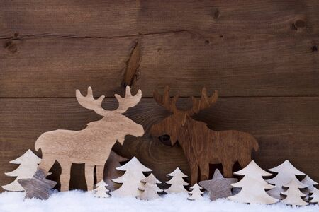 realtionship: Christmas Decoration, Moose Couple In Love On White Snow, Christmas Tree. Rustic, Vintage Wooden Background. Christmas Card For Seasons Greetings.