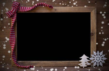 text space: Brown Christmas Blackboard With Copy Space, Free Text As Greeting Card Or Advertisement. Christmas Decoration, Christmas Tree, Snowflakes, Red Loop. Wooden Background. Vintage Rustic Style.