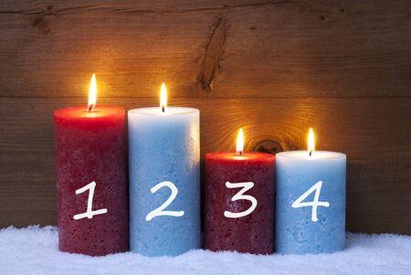 luz de velas: Decoración de Navidad con velas rojas y azules. Cuatro Vela Para Adviento con los números 1, 2, 3, 4. ambiente tranquilo y romántico con velas. Fondo de madera por espacio de copia. Estilo rústico de la vendimia