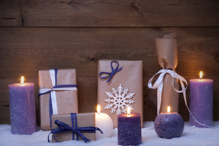 snowflake snow: Christmas Card Or Decoration With Purple Candles, Handmade Christmas Gifts, Presents, Snowflake And Snow. Peaceful Atmosphere With Candlelight. Rustic Vintage Background Stock Photo