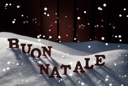 buon: Red Letters On White Snow With Snowflakes As Christmas Card.  Italian Text Or Word Buon Natale Means Merry Christmas. Snowy Scenery And Atmosphere. Rustic Vintage Wooden Background