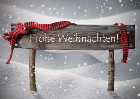 Brown Wooden Christmas Sign On White Snow. Snowy Scenery, Snowflakes. Red Ribbon, German Text Frohe Weihnachten Means Merry Christmas. Christmas Card. Rustic Or Vintage Syle Stock Photo