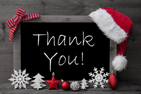 like english: Black And White Blackboard With Red Santa Hat And Christmas Decoration like Snowflake, Tree, Christmas Ball, Fir Cone, Star. English Text Thank You. Wooden Background