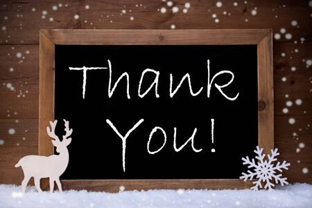 to thank: Brown Christmas Card With Chalkoard, Reindeer And Snowflake On White Snow, Snowflakes. Rustic Vintage Wooden Background. Snowy Decoration With English Text Thank You