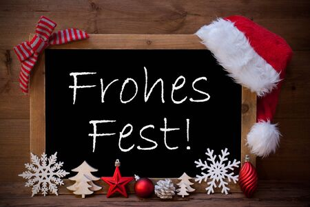 greeting season: Blackboard With Red Santa Hat And Christmas Decoration like Snowflake, Tree, Christmas Ball, Fir Cone, Star. German Text Frohes Fest Means Merry Christmas. Brown Wooden Background Stock Photo