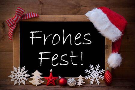 estaciones del año: Pizarra con Santa sombrero rojo y la decoración de Navidad como copo de nieve, árbol, la bola de Navidad, Cono de abeto, la estrella. El texto alemán Frohes Fest Medios Feliz Navidad. Fondo de madera de Brown Foto de archivo