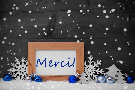 merci: Blue Gray Decoration On Snow. Christmas Tree Balls, Snowflakes And Christmas Tree. Picture Frame With French Text Merci Mean Thank You. Rustic, Vintage Brown Wooden Background. Black And White Image