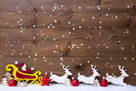 reno: Decoraci�n de Navidad, rojo Santa Claus con el trineo amarillo y negro reno en la nieve, copos de nieve. El fondo de Brown de madera antiguo con Espacio en blanco y bolas de Navidad rojo. Tarjeta de Navidad para los saludos
