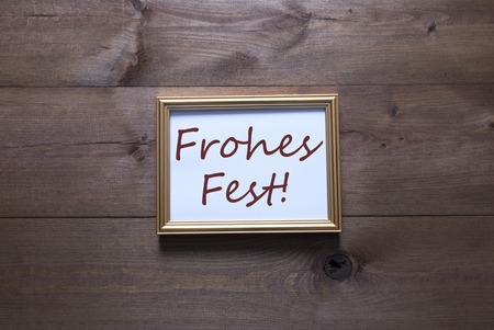 fest: One Golden Picture Frame On Wooden Background. German Text Frohes Fest Means Merry Christmas. Rutic Vintage Or Retro Style. Background With Copy Space As Greeting Card Stock Photo