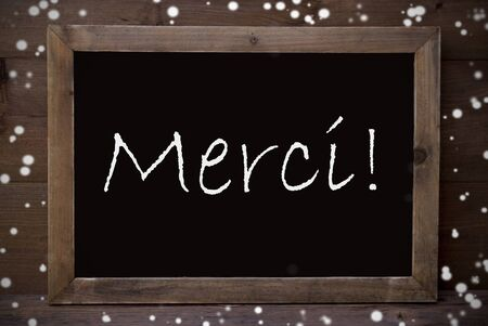 greeting season: Brown Blackboard With French Text Merci Means Thank You As Greeting Card. Wooden Background. Vintage Rustic Style. Snowflakes Symbolizing Christmas Or Winter Season.