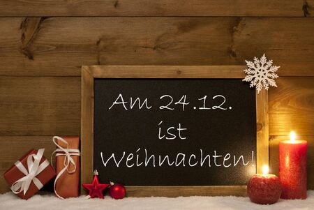 seasons greetings: Festive Christmas Card With Chalkboard, Red Gifts, Christmas Balls, Snowflake And Candles. Christmas Decoration With Vintage Wooden Background. German Text Am 24.12 Ist Weihnachten Mean Christmas Stock Photo