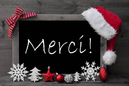 black and white cone: Black And White Blackboard With Red Santa Hat And Christmas Decoration like Snowflake, Tree, Christmas Ball, Fir Cone, Star. FrenchText Danke Merci Thank You. Wooden Background Stock Photo