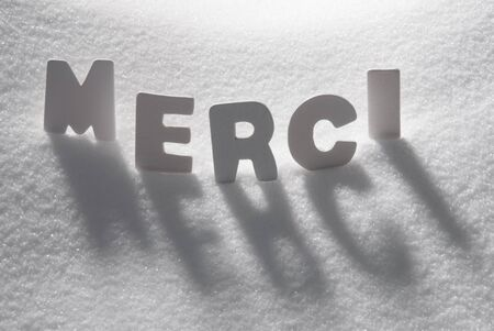 french text: White Letters Building French Text Merci Means Thank You On White Snow