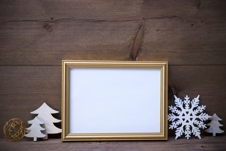free image: Golden Picture Frame With White Christmas Decoration Like Christmas Tree And Snowflake. Copy Space For Advertisement. Vintage Wooden And Retro, Rustic Background. Christmas Card For Seasons Greetings