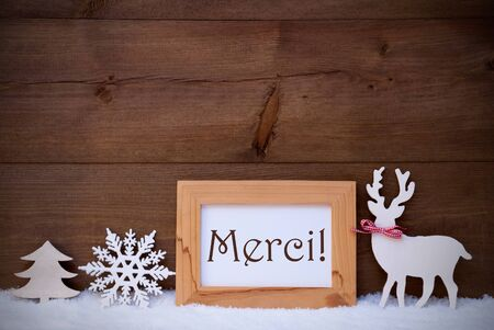 french text: Christmas Card With Brown Picture Frame On White Snow. French Text Merci Means Thank You. White Christmas Decoration Like Snowflake, Tree And Reindeer. Rustic Wooden And Vintage Background Stock Photo
