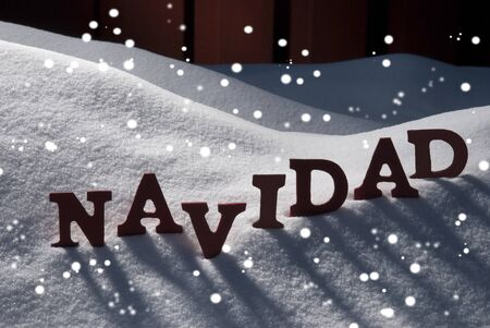 feliz navidad: Red Letters On White Snow As Christmas Card.  Spanish Word Navidad Means Christmas. Snowy Scenery With Snowflakes And Atmosphere. Rustic Vintage Wooden Background Stock Photo