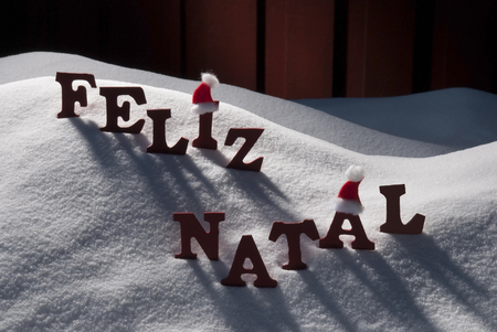 Red Letters With Santa Hat On White Snow As Christmas Card.  Portuguese Text Or Word Feliz Natale Means Merry Christmas. Snowy Scenery And Atmosphere. Rustic Vintage Wooden Background Stock Photo