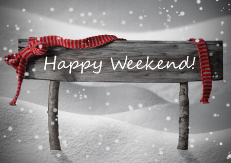 winter scenery: Gray Wooden Christmas Sign On White Snow. Snowy Scenery, Snowflakes. Red Ribbon, English Text Happy Weekend. Christmas Decoration Or Christmas Card. Rustic Or Vintage Syle.Black And White Image