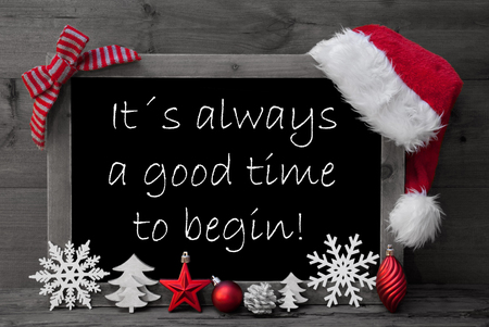 like english: Black And White Blackboard With Red Santa Hat And Christmas Decoration like Snowflake, Tree, Christmas Ball, Fir Cone, Star. English Quote It Is Always A Good Time To Begin. Wooden Background